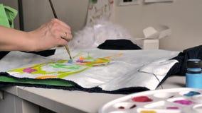 La mano femenina aplica la pintura rosada en tela con un modelo usando un cepillo