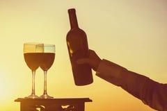 La mano femenina con la botella vierte el vino rojo en los vidrios en un fondo de la puesta del sol Imagenes de archivo