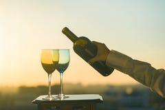 La mano femenina con la botella vierte el vino rojo en los vidrios en un fondo de la puesta del sol Imagen de archivo libre de regalías