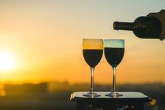 La mano femenina con la botella vierte el vino rojo en los vidrios en un fondo de la puesta del sol Fotografía de archivo