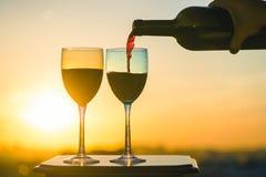 La mano femenina con la botella vierte el vino rojo en los vidrios en un fondo de la puesta del sol Imagen de archivo