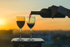 La mano femenina con la botella vierte el vino rojo en los vidrios en un fondo de la puesta del sol Fotografía de archivo libre de regalías
