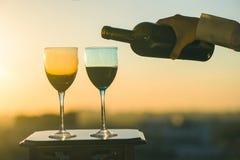 La mano femenina con la botella vierte el vino rojo en los vidrios en un fondo de la puesta del sol Imágenes de archivo libres de regalías