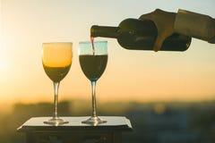 La mano femenina con la botella vierte el vino rojo en los vidrios en un fondo de la puesta del sol Foto de archivo