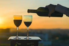 La mano femenina con la botella vierte el vino rojo en los vidrios en un fondo de la puesta del sol Fotos de archivo libres de regalías