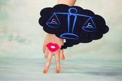 La mano femenina con dos fingeres abajo sonríe y los labios rojos en un fondo azul y una igualdad regional de los pensamientos foto de archivo libre de regalías
