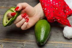 La mano femenina con la manicura festiva hermosa del ` s del Año Nuevo sostiene el aguacate cortado por los anillos Fotos de archivo