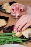 La mano femenina con la manicura hermosa guarda un vaso de medida con la vodka Fotos de archivo libres de regalías