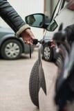 La mano femenina con llave abre la puerta de coche Foto de archivo libre de regalías