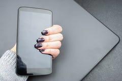 La mano femenina con los clavos oscuros sostiene un teléfono móvil, que miente en un ordenador portátil cerrado imagen de archivo