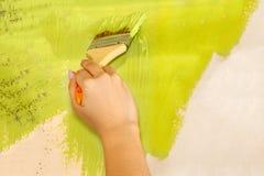 La mano femenina con un cepillo plano con la pintura verde pinta la pared casera fotografía de archivo libre de regalías