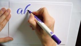 La mano femenina del vídeo de movimiento escribe un alfabeto caligráfico en oficina almacen de video