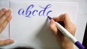 La mano femenina del vídeo de movimiento escribe un alfabeto caligráfico en oficina almacen de metraje de vídeo