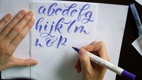 La mano femenina del vídeo de movimiento escribe un alfabeto caligráfico en oficina metrajes