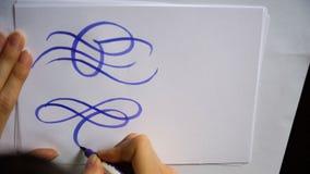 La mano femenina del vídeo de movimiento escribe un flourish caligráfico en la hoja de papel en oficina almacen de video