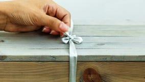 La mano femenina desata la cinta en la caja de madera del regalo almacen de metraje de vídeo