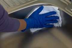 La mano femenina en los guantes de goma limpia el fregadero con un paño seco imagen de archivo libre de regalías