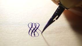 La mano femenina escribe a pluma muestras caligráficas almacen de metraje de vídeo