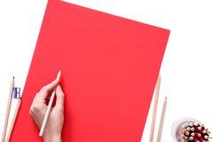 La mano femenina está lista para dibujar con se corrige en el papel rojo Aislado en blanco Imagen de archivo