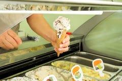 La mano femenina está sosteniendo una vainilla con helado de los frutos secos en cono de la galleta Refrigerador del helado con l Fotos de archivo libres de regalías