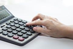 La mano femenina está tocando los botones en la calculadora, cerrado-para arriba y aislado en el fondo blanco imagen de archivo