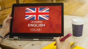 La mano femenina está tocando una tableta inglesa de la pantalla del símbolo Imagen de archivo libre de regalías