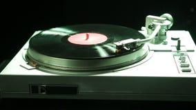 La mano femenina fija una aguja de la placa giratoria en un disco de vinilo en luz del color almacen de video