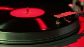 La mano femenina fija una aguja de la placa giratoria en un disco de vinilo en luz del disco almacen de metraje de vídeo