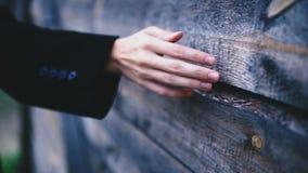 La mano femenina fina en un fondo de una casa de madera metrajes