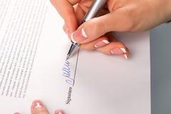 La mano femenina firma la carta comercial Fotos de archivo