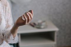 La mano femenina guarda el perfume Fotos de archivo
