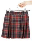 La mano femenina guarda la falda de tela escocesa Fotos de archivo