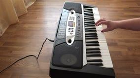 La mano femenina hermosa con los clavos rojos compone música en el teclado pulsando las teclas blancas almacen de video