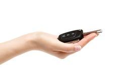 La mano femenina lleva a cabo llaves del coche en el fondo blanco Imagen de archivo