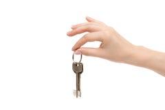 La mano femenina lleva a cabo llaves en el fondo blanco Imágenes de archivo libres de regalías