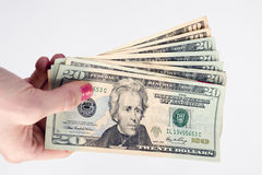 La mano femenina lleva a cabo moneda del pago al contado dinero de veinte dólares Fotos de archivo
