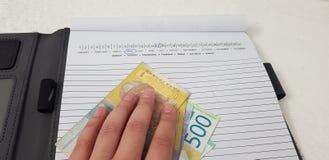 La mano femenina pone en billetes de banco del hryvnia fotografía de archivo