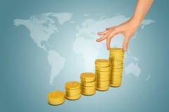 La mano femenina pone la moneda en la pila de monedas Imagen de archivo libre de regalías