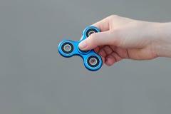 La mano femenina que lleva a cabo el juguete popular del hilandero de la persona agitada en fondo gris, el juguete del alivio de  Imagenes de archivo