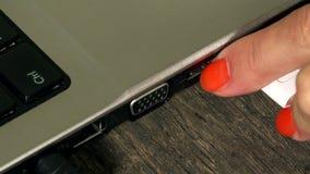 La mano femenina quita el alambre blanco del cable del USB del ordenador portátil primer almacen de video