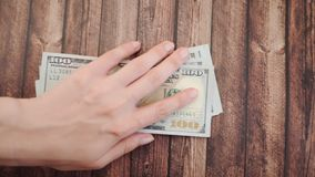 La mano femenina se lleva dólares de los centenares en una tabla de madera Cámara lenta almacen de video