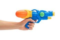 La mano femenina sostiene el azul arroja a chorros el arma Aislado en el fondo blanco fotos de archivo
