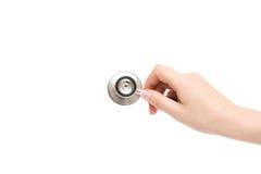 La mano femenina sostiene el estetoscopio en un fondo blanco Fotografía de archivo libre de regalías