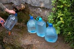 La mano femenina sostiene la botella plástica con agua Foto de archivo libre de regalías