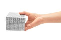 La mano femenina sostiene la caja de regalo blanca con los pequeños círculos Aislado en el fondo blanco Foto de archivo libre de regalías