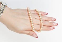 La mano femenina sostiene la cuerda de rosca de las perlas Imagen de archivo libre de regalías