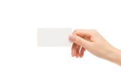 La mano femenina sostiene la tarjeta blanca en un fondo blanco Fotografía de archivo libre de regalías