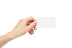 La mano femenina sostiene la tarjeta blanca en un fondo blanco Imagen de archivo