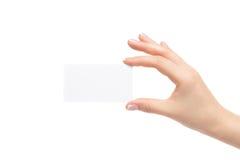 La mano femenina sostiene la tarjeta blanca en un fondo blanco Fotografía de archivo