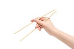 La mano femenina sostiene los palillos en un fondo blanco Fotos de archivo